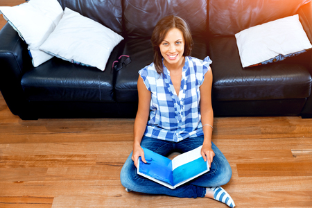 Happy woman reading a book on the floor