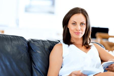 Happy woman reading a book sitting on a sofa