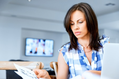Woman with papers in their living room Stock Photo