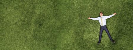 Pensive businessman on grass