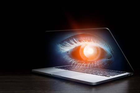 Laptop with human eye on screen on dark background Stock fotó