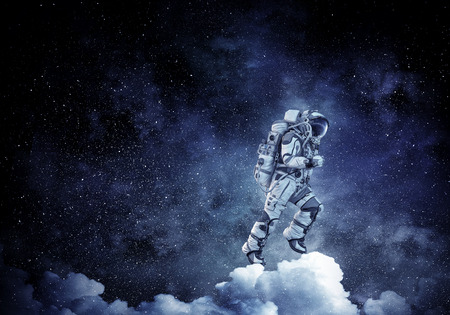 Astronaut running on white clouds in dark sky. Mixed media