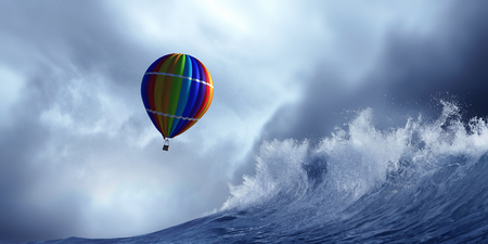 Colored aerostat flying above stromy sea. Mixed media Stock Photo