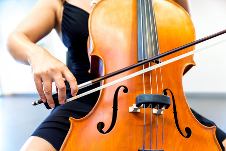 Cellist playing violoncello musical instrument of orchestra