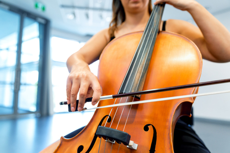 Close up of cello with bow in hands Stockfoto