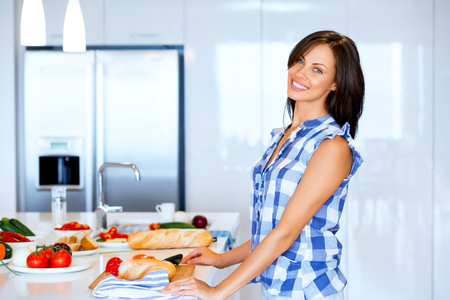Beautiful woman standing in the kitchen and smiling Фото со стока - 113720104
