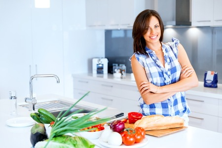 Beautiful woman standing in the kitchen and smiling Stock Photo