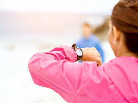 Woman in sportswear using smartwatch
