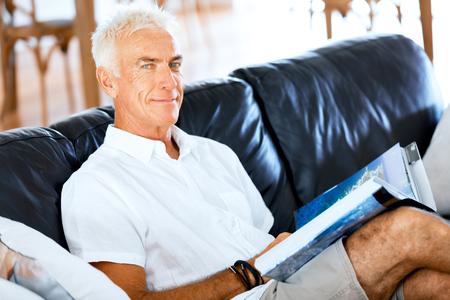 Handsome sennior man reading a book relaxing on a sofa