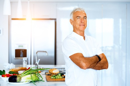 Portrait of a smart senior man standing in kitchen