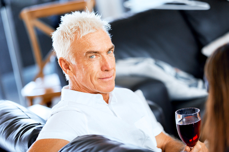Senior man with holding a glass of wine indoors