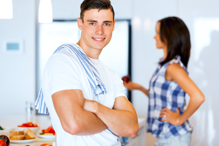 Young man standing in the kitchen and smiling
