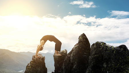 man doing complex Yoga exercise headstand. Amazing Yoga landscape in beautiful mountains. Dangerous stunts traceur standing on his hands on the edge of a cliff. Stock Photo