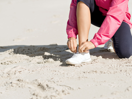 Young sports woman runner tying shoelace on wooden boardwalk at the seaside Stock Photo - 115487572