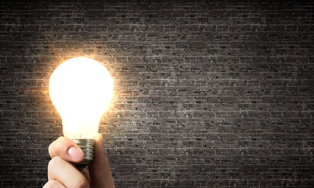 Glowing light bulb in hand as symbol for bright idea 版權商用圖片
