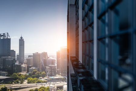 Modern business city building and rays of sunrise