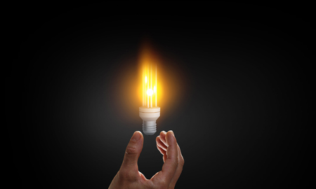 Business hand holding glowing light bulb against