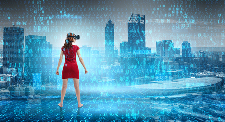 Woman in red dress wearing virtual reality helmet. Mixed media Stock Photo