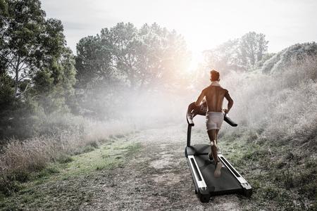 Back view of man athlete running on treadmill. Mixed media
