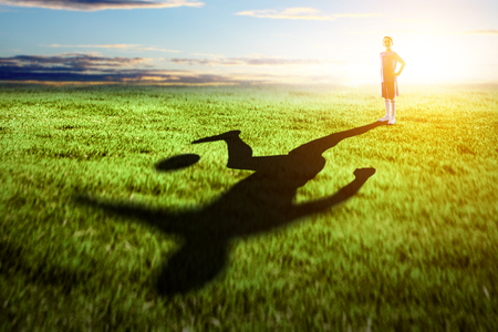 Little soccer champion on green field and his shadow on grass. Mixed media Stock Photo