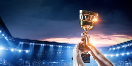Hand of athlete holding cup trophy against stadium. Mixed media 스톡 콘텐츠