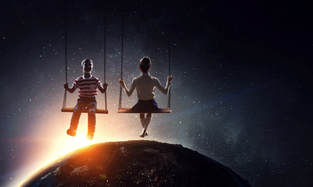 Cute little girl and boy riding on swing. Stock Photo