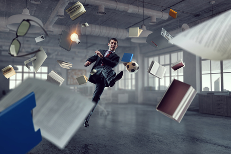 Playing football in office. Mixed media Stock Photo