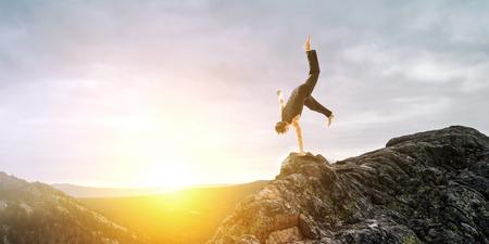 Amazing yoga man doing one handstand on rock edge. Mixed media
