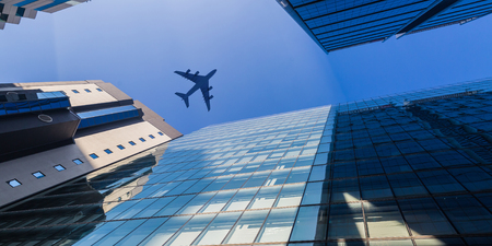 Bottom angle view of airplane in sky over city buildings