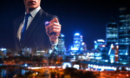 Businessman against modern city background draw on screen