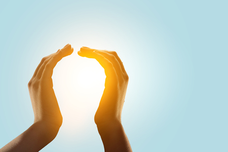 Glowing light bulb in male hands on white background 写真素材
