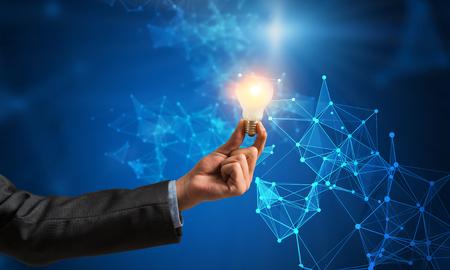 Main d'affaires tenant une ampoule rougeoyante contre. rendu 3D Banque d'images