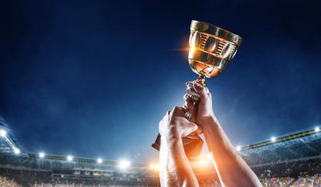 Mano de atleta sosteniendo el trofeo de la copa contra el estadio. Técnica mixta