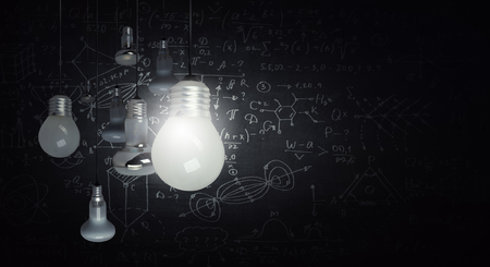 Glowing glass light bulb hanging from above and business sketches at dark background. Mixed media 스톡 콘텐츠 - 116425338