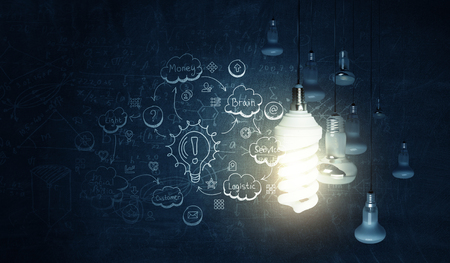 Glowing glass light bulb hanging from above and business sketches at dark background. Mixed media