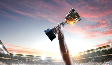 Hand of athlete holding cup trophy against stadium. Mixed media Stock fotó