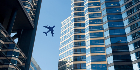 Airplane above business city