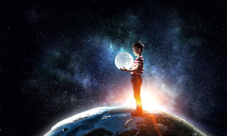 Le garçon tient la lune. Technique mixte Banque d'images