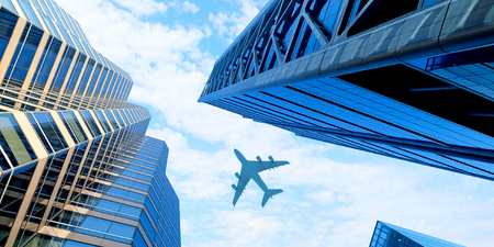 Airplane above business city Stock Photo - 118986073
