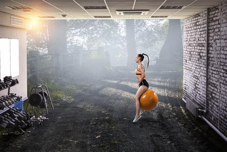 Sporty woman on fitness ball. Mixed media Stock Photo - 118977240