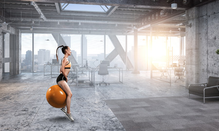 Sporty woman on fitness ball. Mixed media Stock Photo - 118894668