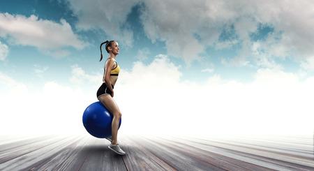 Sporty woman on fitness ball. Mixed media Stock Photo - 118883448