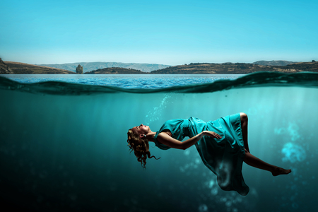 Woman dancer in clear blue water Stock Photo