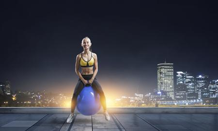 Sporty woman on fitness ball. Mixed media Stock Photo - 119576526