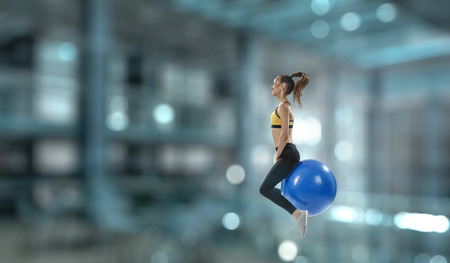 Sporty woman on fitness ball. Mixed media Stock Photo - 119495171