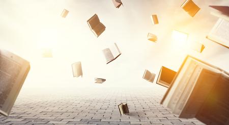 Open books flying around on light sky background Stok Fotoğraf