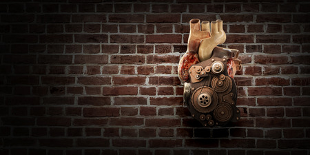 Anatomic heart model made with gears and mechanic parts, brickwall background