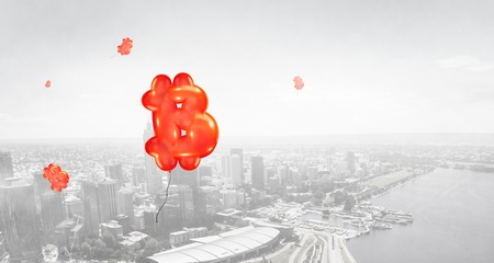 Red bitcoin marks flying like balloons in the air of a city, upper view