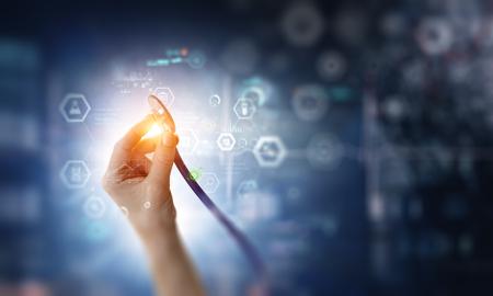 Ärztin Hand mit Stethoskop und Netzdiagrammen und Symbolen. Gemischte Medien