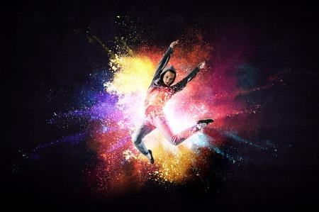 Moderne Tänzerin, die in Hoodie mit buntem Spritzerhintergrund springt. Gemischte Medien
